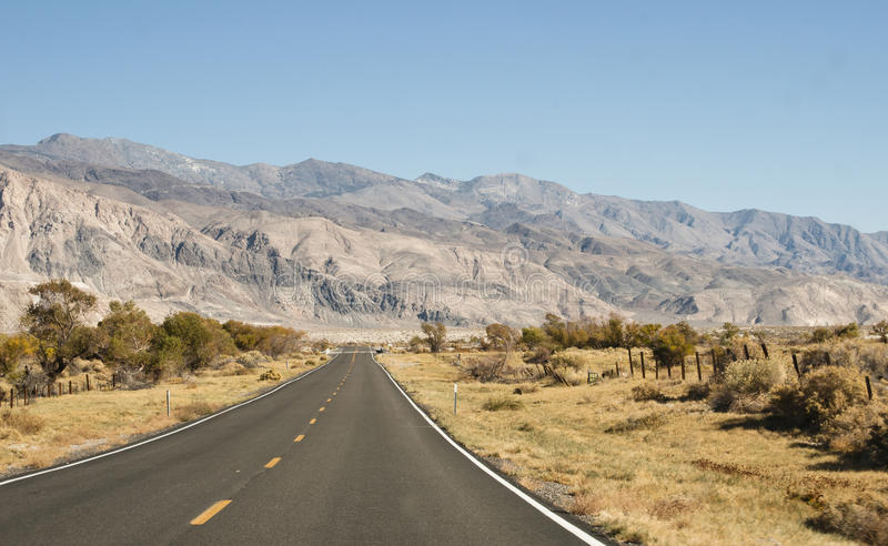 Straight road section trough the desert and mountains stock images