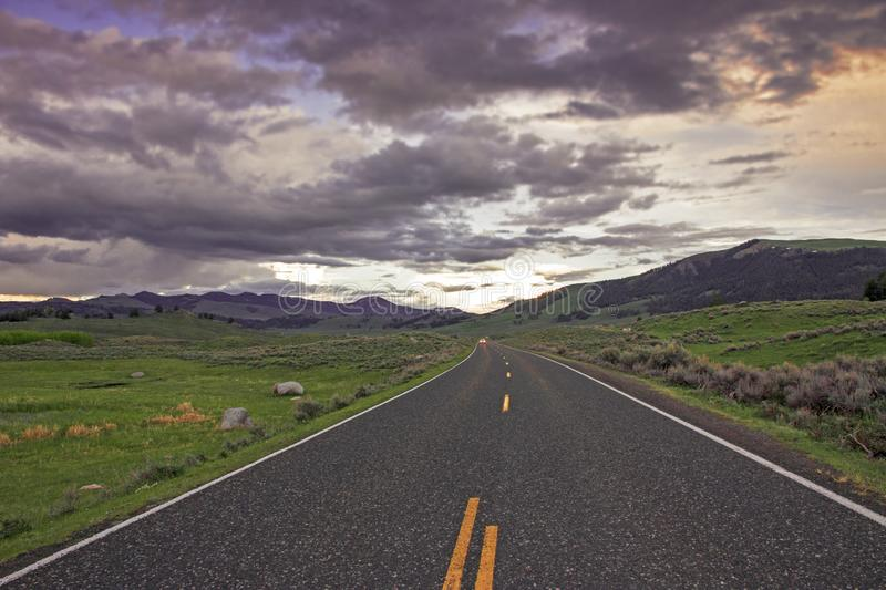 Road towards Yellowstone National Park. Straight Road towards Yellowstone National Park during sunset in Wyoming, USA stock photo