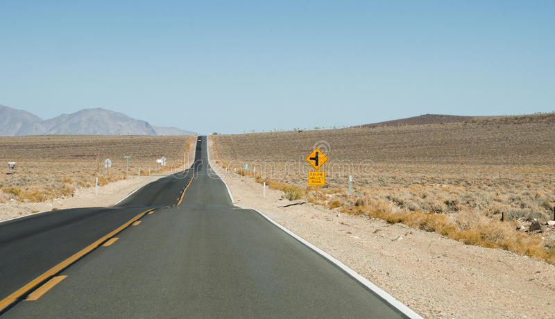 Straight section of Saline Valley Road and yellow traffic sign royalty free stock photography