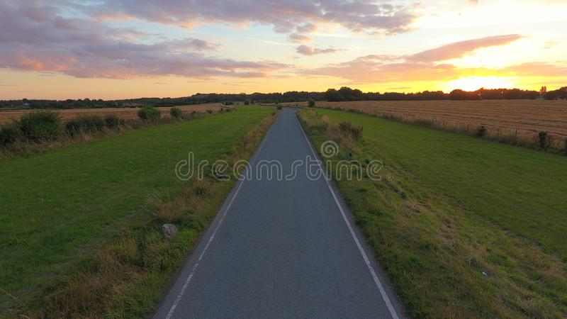 Straight Tarmac Road Sunset. A straight road leads to the horizon where the sun is setting royalty free stock photography
