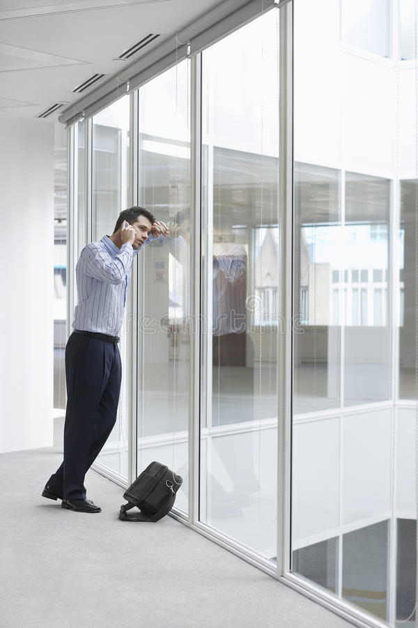 Strained Businessman Using Cellphone In Office. Full length of strained young businessman using cellphone in empty office space royalty free stock photo