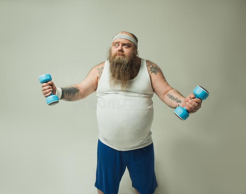Thick bearded guy lifting dumbbells with effort royalty free stock images