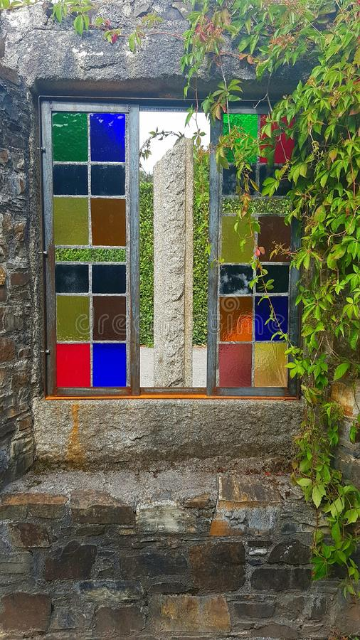 Strained glass window, garden feature. A old Strained glass window, garden feature disused old garden building . Mount Edgecombe , Cornwall royalty free stock photos