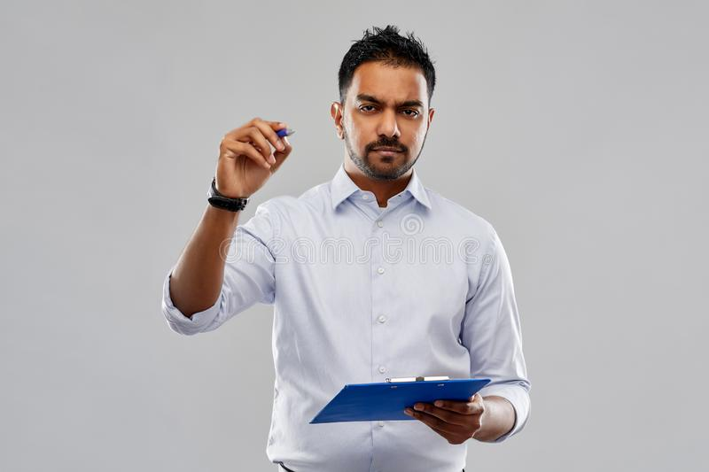 Strained indian businessman writing to clipboard. Business, office worker and people concept - strained indian businessman writing to clipboard over grey stock images