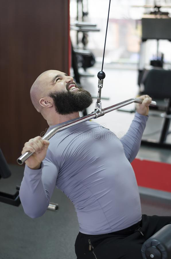 Strained young man working out in the gym, sports exercises for healthy life. Stock footage royalty free stock photo