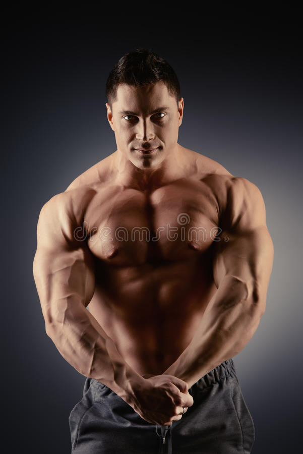 Straining muscles. Handsome muscular bodybuilder posing over black background royalty free stock photo