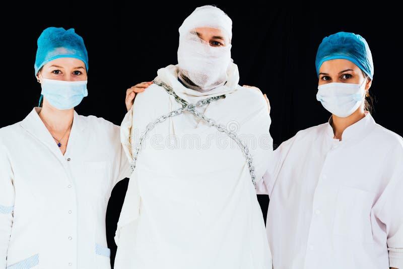 Straitjacket mężczyzna uspokajał puszek pielęgniarkami fotografia stock