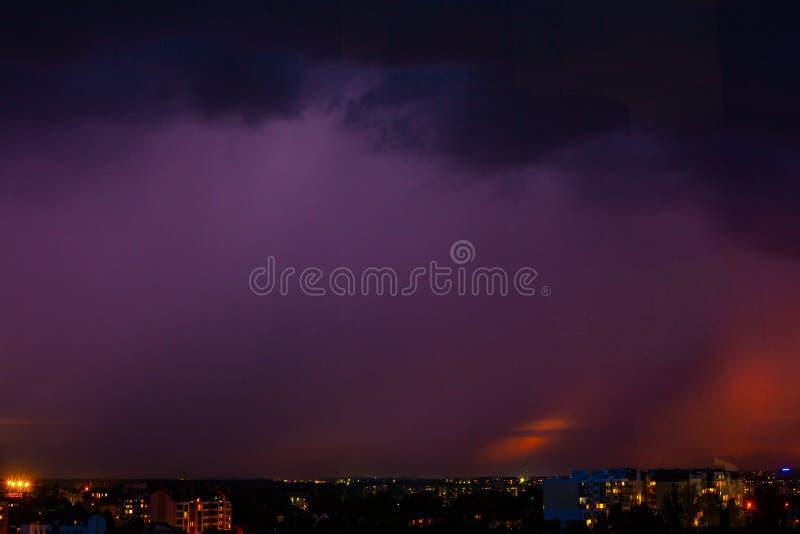 Strajk pioruna nad miastem, purpurowe światło fotografia stock