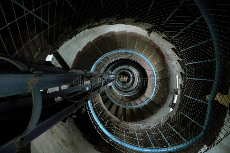 Strak windende cementwenteltrap binnen van een vuurtoren met een blauw traliewerkperspectief die neer vanaf de bovenkant kijken stock afbeelding