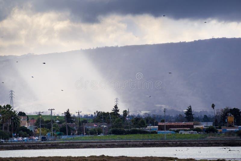 Stralen die van licht door donkere onweerswolken overgaan royalty-vrije stock afbeelding