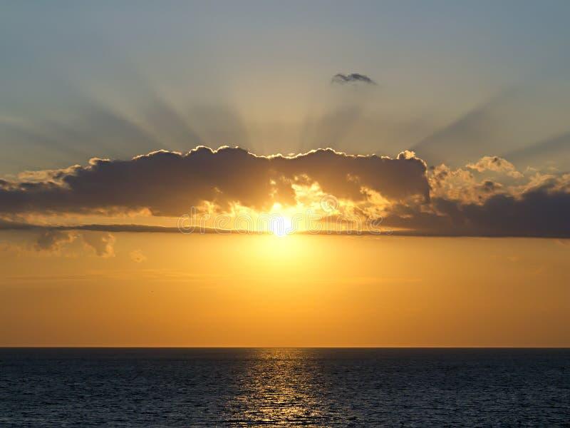 Stralen van de plaatsende zononderbrekingen door de wolken stock afbeelding