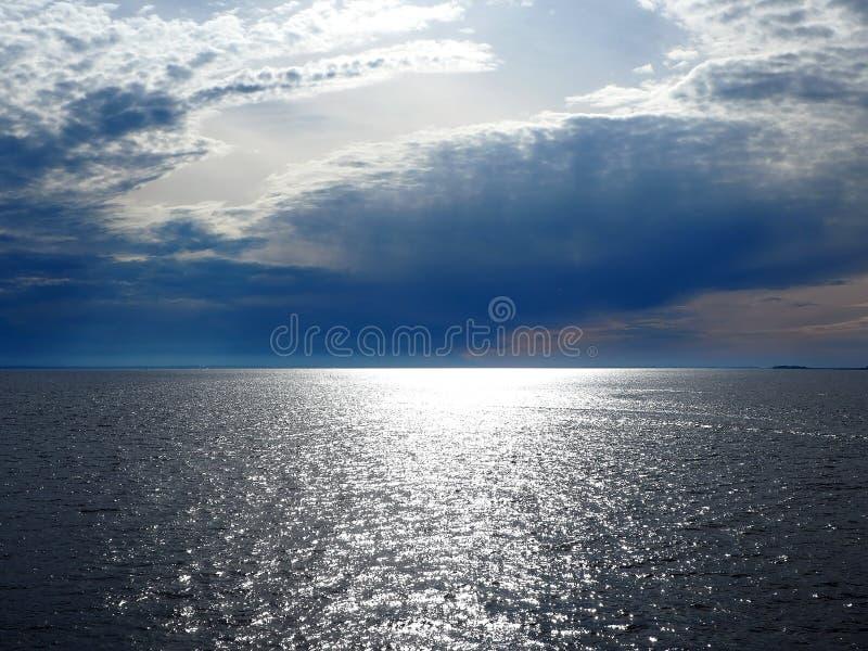 Stralen van de zon door onweerswolken over het overzees stock afbeeldingen