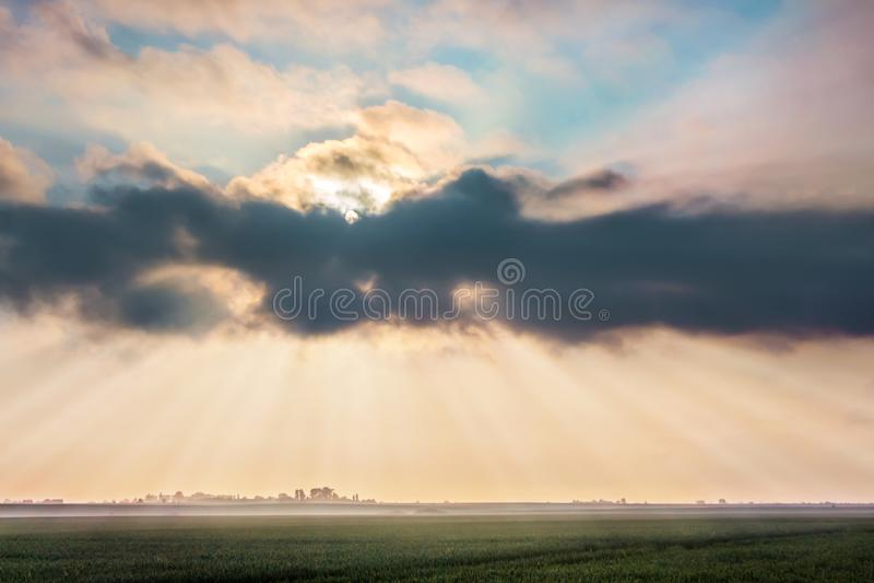 Stralen van zon die een donkere wolk over tarwegebied dur doorbladeren royalty-vrije stock foto