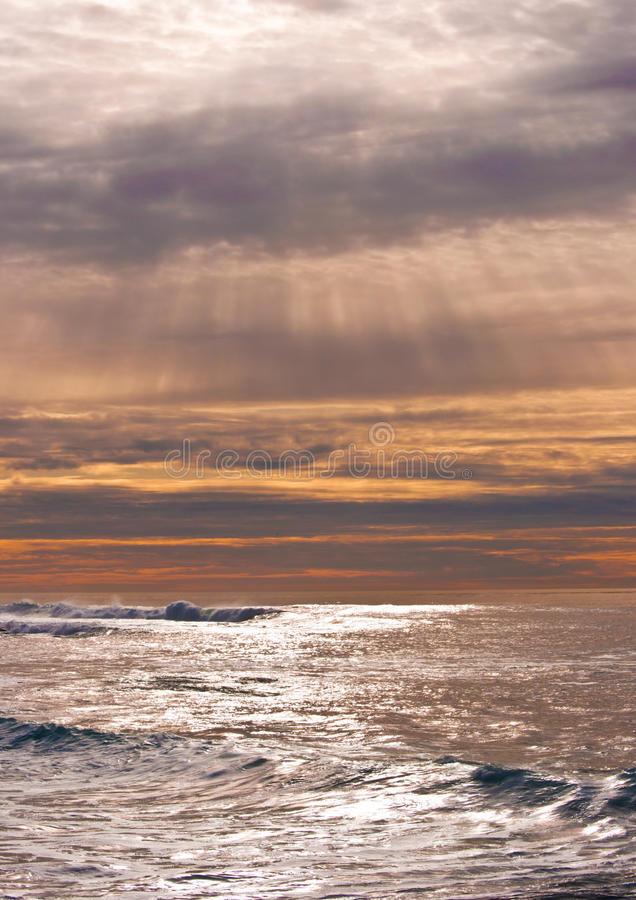 Stralen van zonlicht over oceaangolven royalty-vrije stock afbeelding