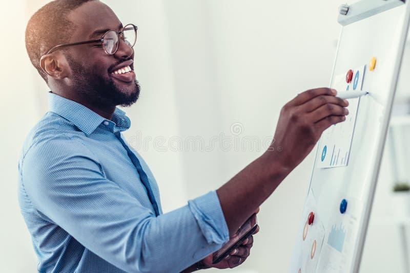Stralende millennial werknemer die presentatie in bureau voorbereiden royalty-vrije stock afbeeldingen