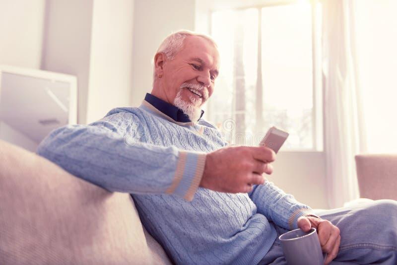 Stralende oudste die zijn nieuwe mobiele telefoon controleren stock afbeelding