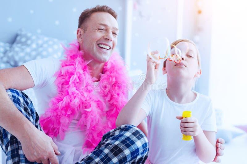Stralende vader en dochter blazende zeepbels royalty-vrije stock foto