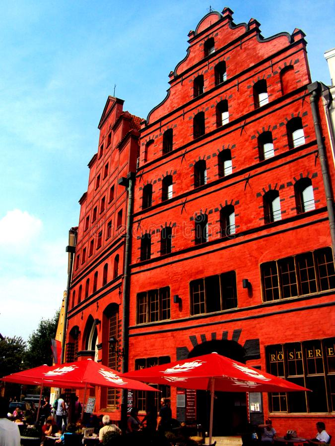 STRALSUND, GERMANY, August 2014 - Ancient red brick building with cafe and blue sky in the city of Stralsund royalty free stock photo