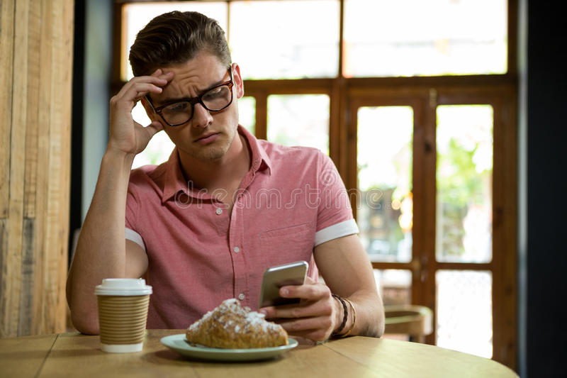 Stramad åt man som använder den smarta telefonen i coffee shop royaltyfria foton