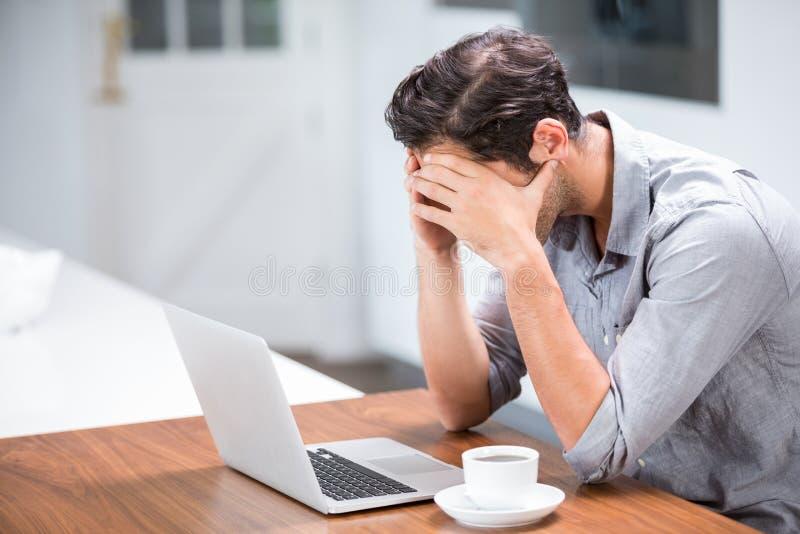 Stramad åt ung man med huvudet i händer arkivfoto