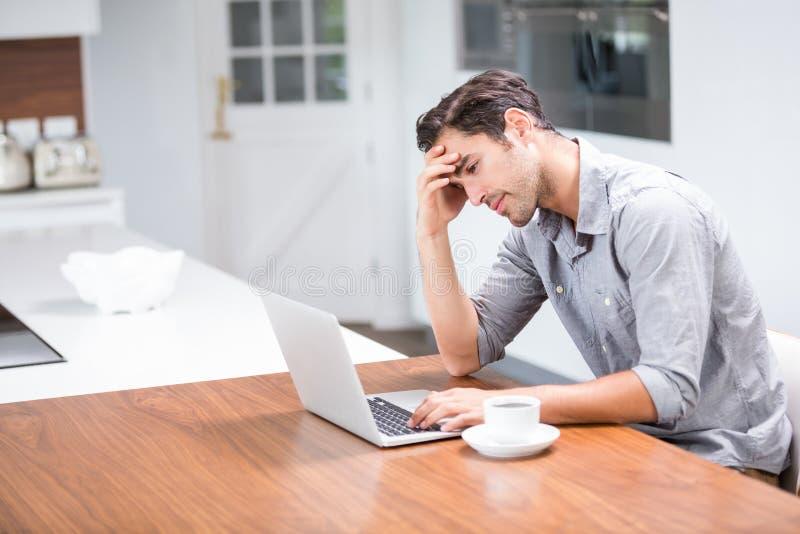 Stramad åt ung man som använder bärbara datorn royaltyfri foto