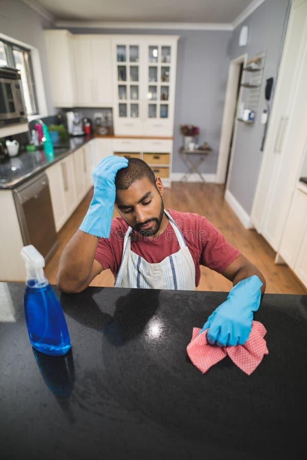 Stramad åt ung man vid marmorräknaren i kök royaltyfri foto