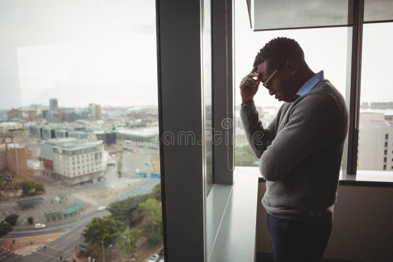 Stramat åt utövande stående near fönster arkivbild