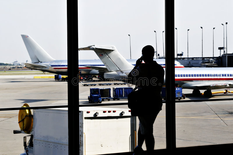 Strand Air Traveler. Waiting at Airport making phone call royalty free stock image