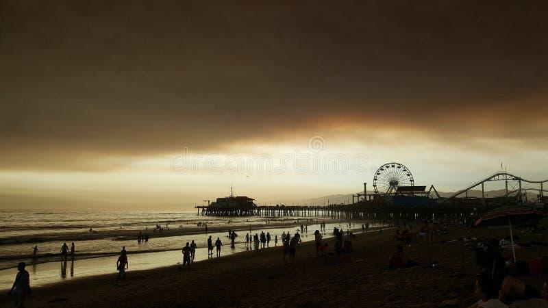 Strand bei Sonnenuntergang mit dunkler Bewölkung stockfotografie