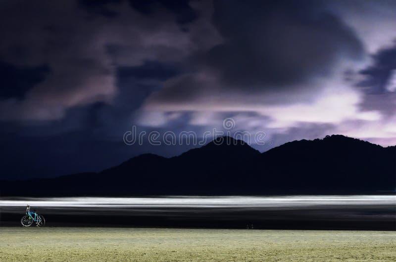 Strand bij nacht met zand, overzeese golven en bergen stock fotografie