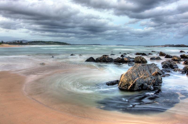 Strand bij schemer met wolken royalty-vrije stock foto