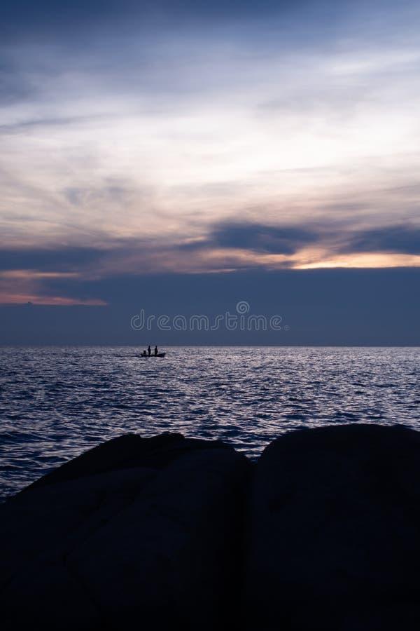 Strand bij zonsondergang met het leven van een kleine vissersboot in het overzees royalty-vrije stock fotografie