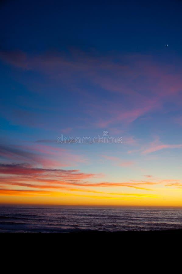 Strand bij zonsondergang met maan royalty-vrije stock fotografie
