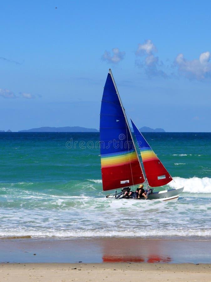 Strand: catamaran die in branding vaart - sluit stock afbeelding