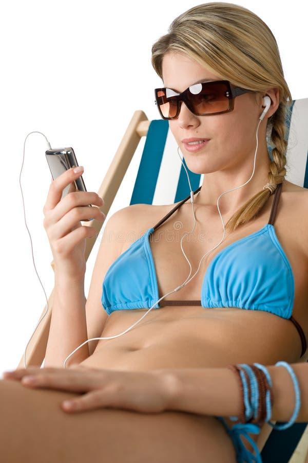 Strand - de Gelukkige vrouw ontspant in bikini met muziek royalty-vrije stock afbeeldingen