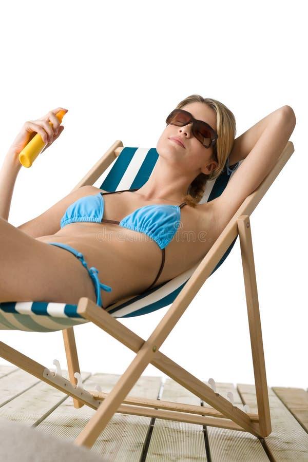 Strand - de Jonge vrouw in bikini past zonnebrandolie toe stock foto