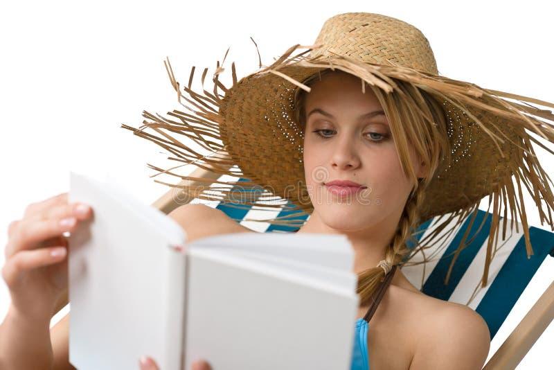 Strand - de Jonge vrouw ontspant met boek in bikini royalty-vrije stock afbeelding