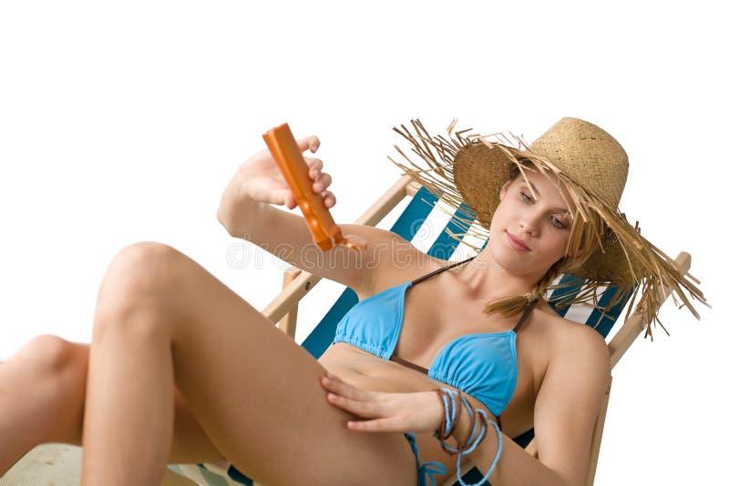 Strand - de Jonge vrouw past zonnebrandolie toe stock foto's