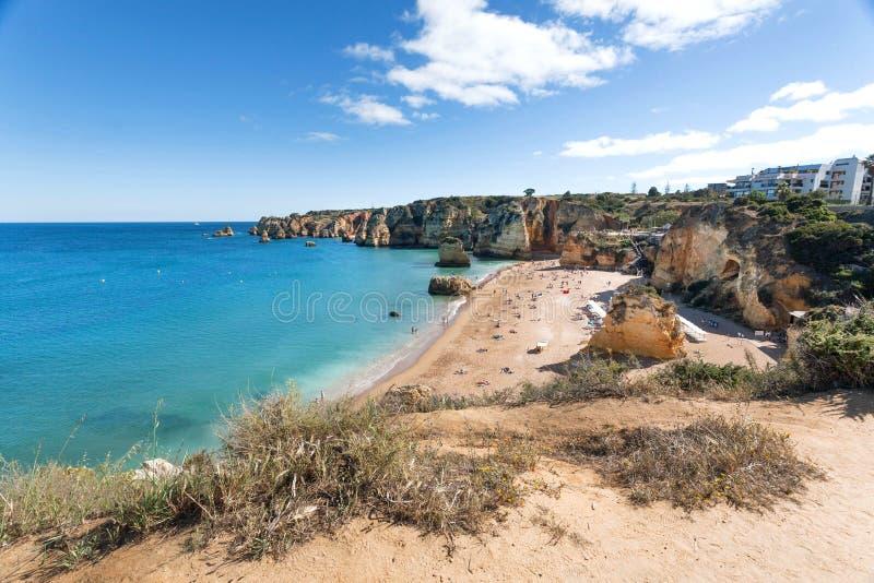 Strand in de stad van Portugal Oceaangolven op vreedzame kust bij zonnige dag van Algarve gebied stock afbeeldingen