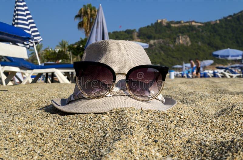 Strand in de zomer Op het zand ligt een vrouwen` s hoed met glazen stock foto
