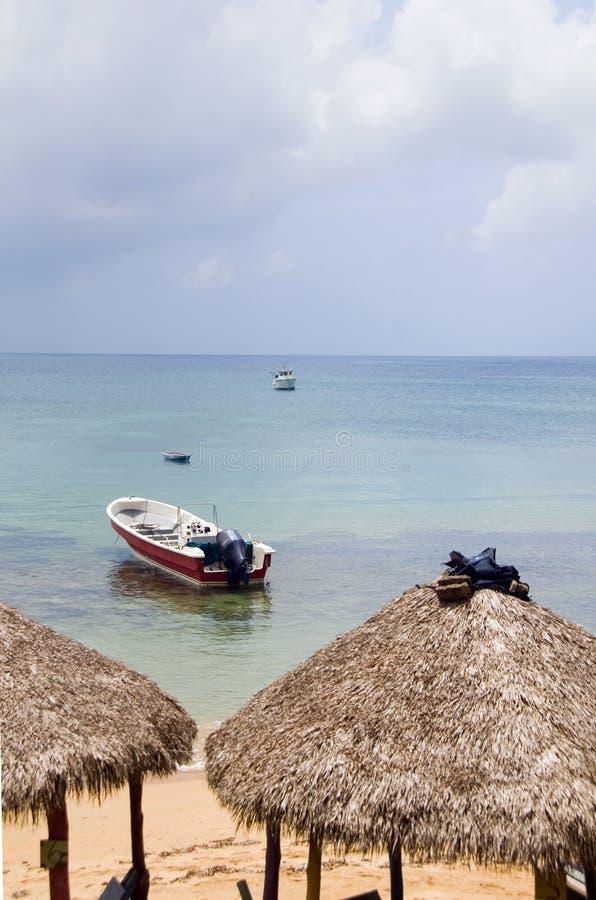 Strand decken Dachrestauranthütten mit Fischerboot karibischem Se mit Stroh stockfotografie