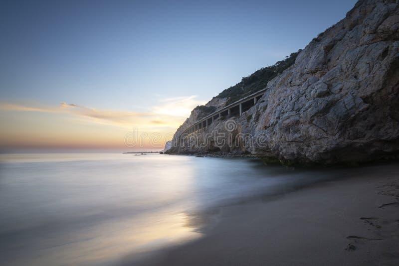 Strand in der ruhigen felsigen Landschaft bei Sonnenuntergang stockfotos
