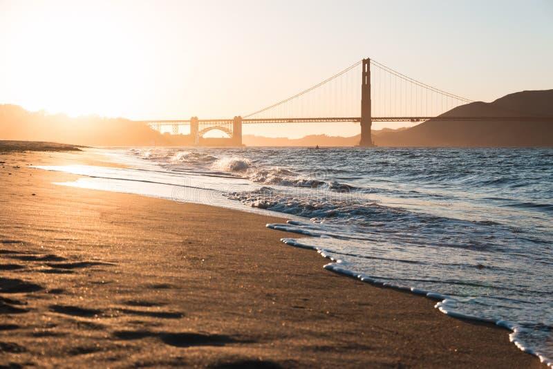 Strand en gouden poort bij zonsondergang stock afbeeldingen