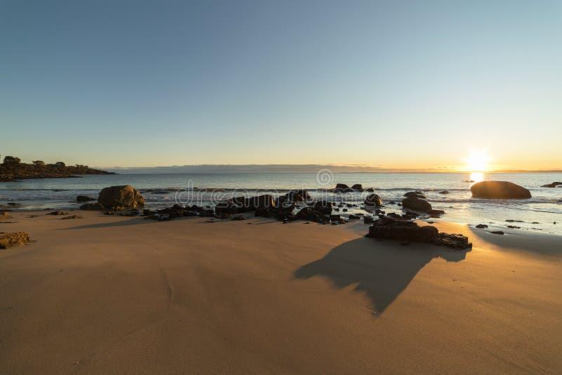 Strand en rotsen tijdens de zonsondergang stock fotografie