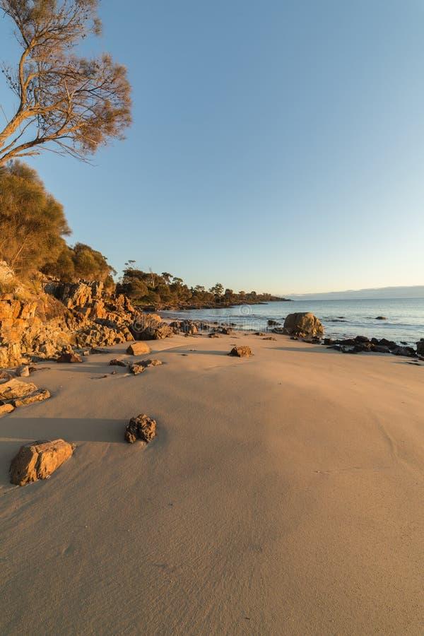 Strand en rotsen tijdens de zonsondergang royalty-vrije stock afbeelding
