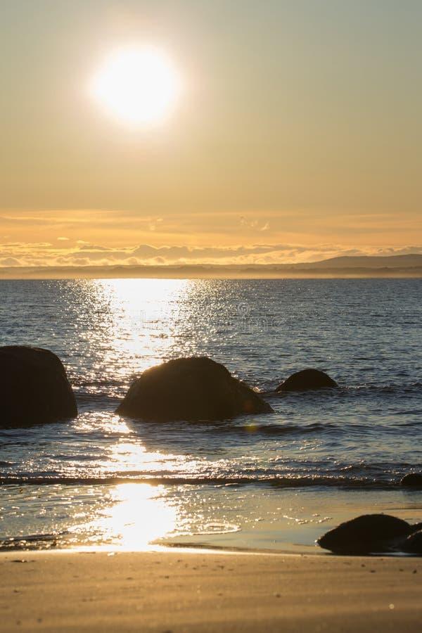 Strand en rotsen tijdens de zonsondergang stock foto's