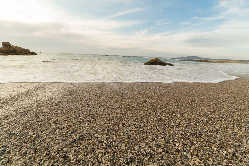 Strand en rotsen tijdens de zonsondergang stock afbeeldingen