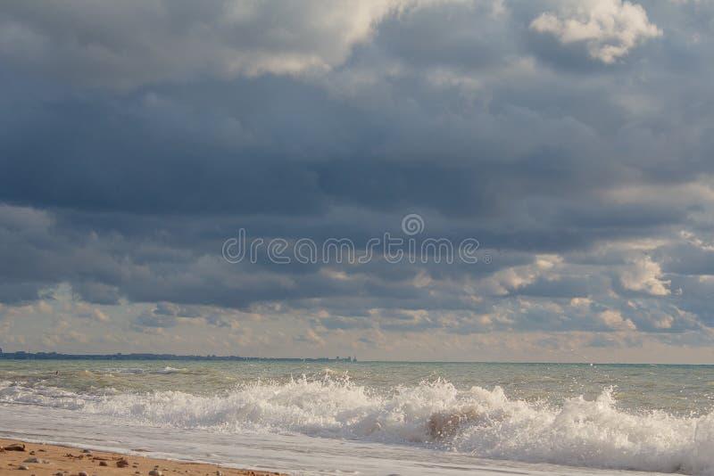 Strand en stad op de horizon in stormachtig weer royalty-vrije stock afbeelding