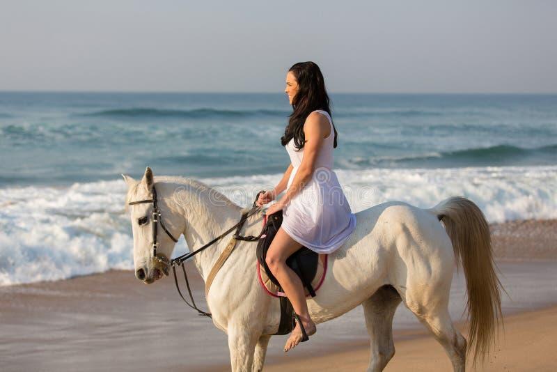 Strand för flickaridninghäst arkivfoto
