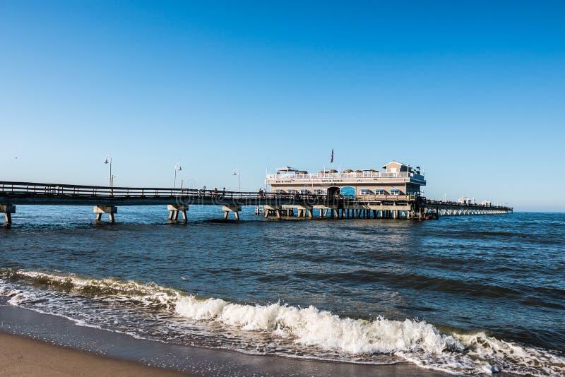 Strand för havsikt i vår med folk på pir fotografering för bildbyråer